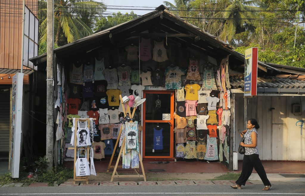 In this Friday, May 10, 2019, photo, a Sri Lankan walks past a souvenir shop in Hikkaduwa, Sri Lanka. Sri Lanka was the Lonely Planet guide's top trav...