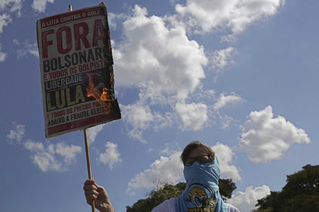 "A masked student burns a poster with a message that reads in Portuguese: ""Out Bolsonaro"" during an education strike in Brasilia, Brazil, Wednesday, Ma..."