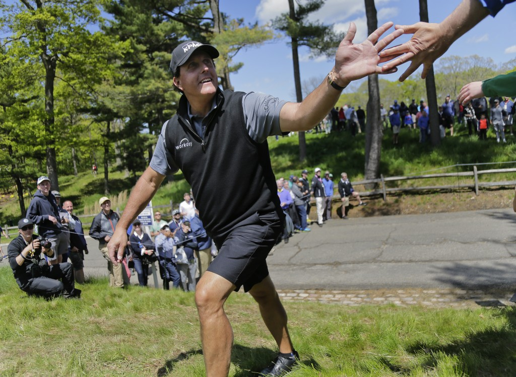 Phil Mickelson greets fans on his way to the 13th tee during a practice round for the PGA Championship golf tournament, Wednesday, May 15, 2019, at Be