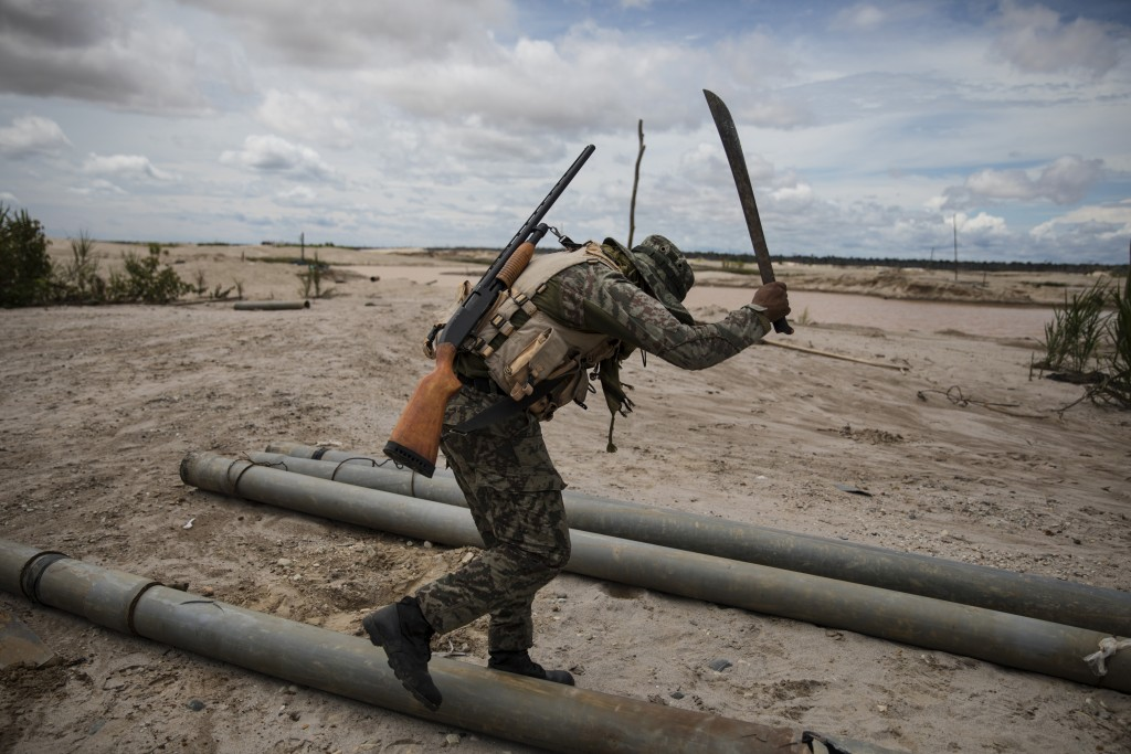 """In this March 27, 2019 photo, a soldier hacks with a machete tubing used by illegal miners to mine gold, as part of """"Operation Mercury"""", in Peru's Tam"""