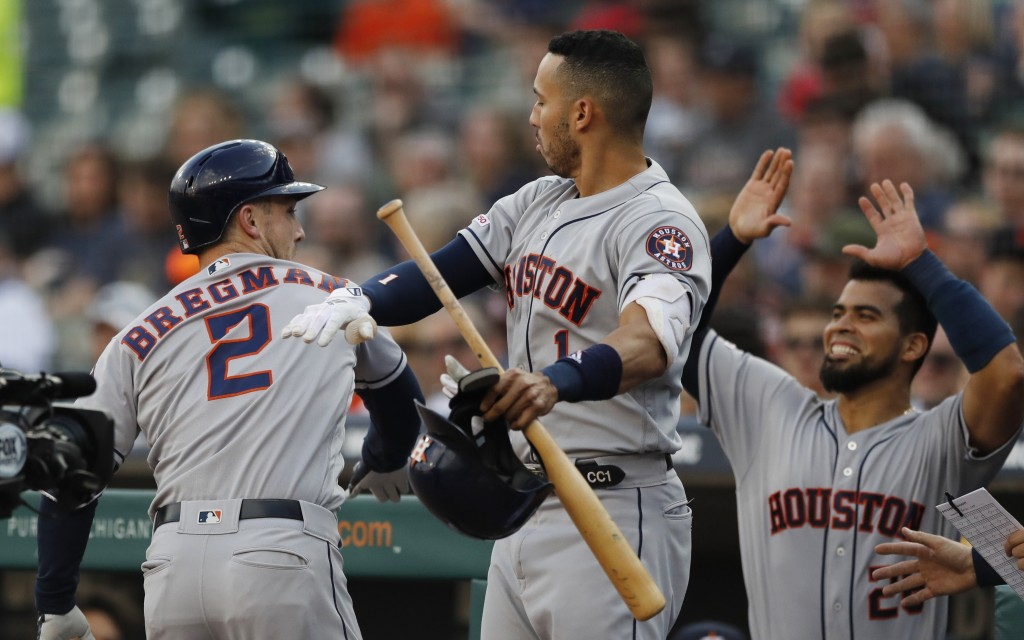 Houston Astros' Alex Bregman (2) is greeted by teammates Carlos Correa (1) and Robinson Chirinos (28) after hitting a solo home run during the first i...