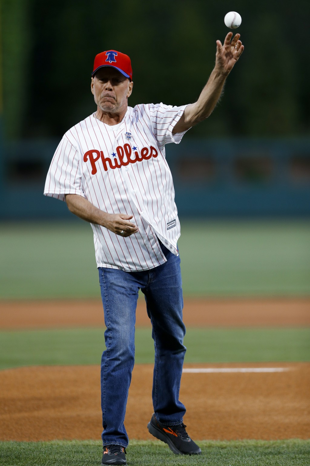 Actor Bruce Willis throws out a first pitch before a baseball game between the Philadelphia Phillies and the Milwaukee Brewers, Wednesday, May 15, 201...