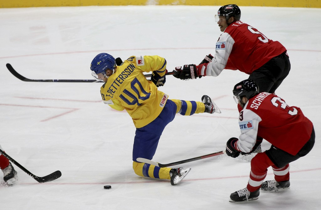 Sweden's Elias Pettersson, left, checks Austria's Thomas Raffl and Peter Schneider, right, during the Ice Hockey World Championships group B match bet...