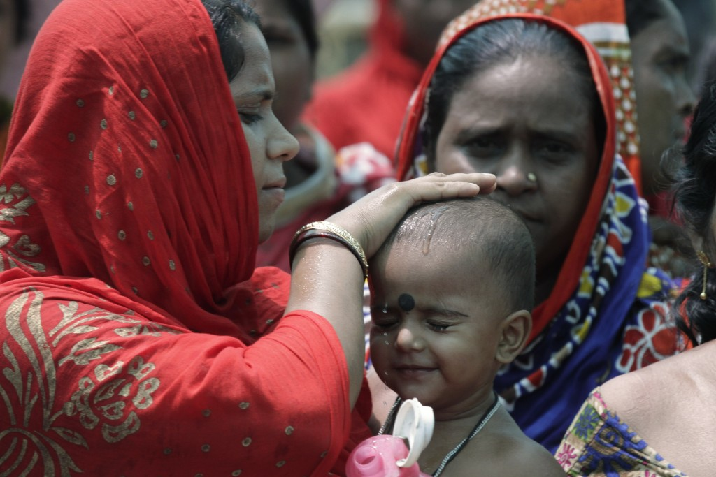 A woman wets the head of a child during an election rally addressed by Trinamool Congress leader and Chief Minister of West Bengal state Mamata Banerj