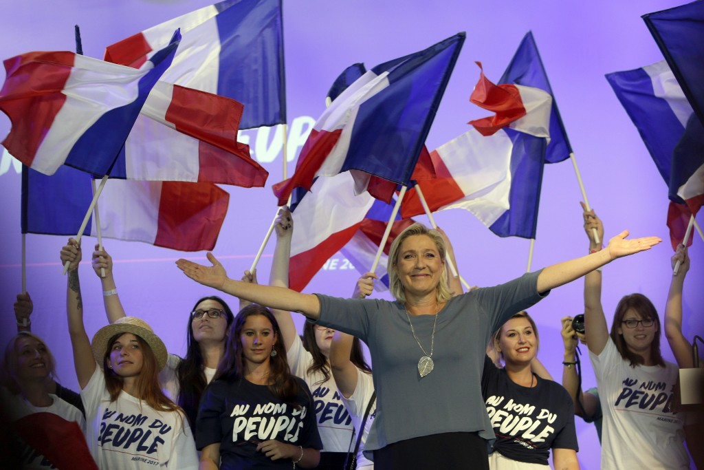 FILE - In this Sunday, Sep. 18, 2016 file photo, far-right National Front president Marine Le Pen, waves to supporters during a meeting in Frejus, sou
