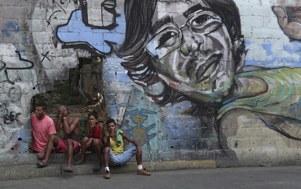 A group of young people rest in a hole in the wall at the Agua Salud neighborhood of Caracas, Venezuela, Wednesday, May 15, 2019. More than 3 million