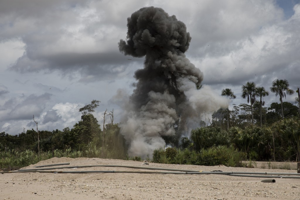 "In this March 27, 2019 photo, a cloud of smoke rises after police dynamite machinery used by illegal miners as part of ""Operation Mercury"", in Peru's ..."
