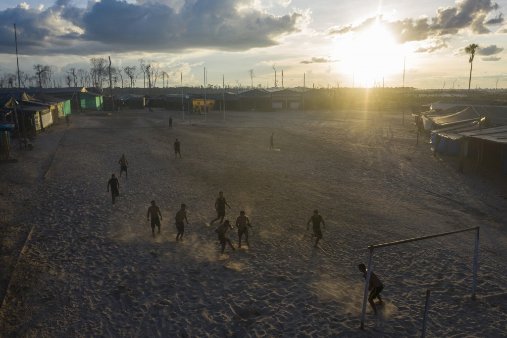 "In this March 31, 2019 photo, ""Operation Mercury"" soldiers play soccer at the Balata police and military base in Peru's Tambopata province. As night f..."