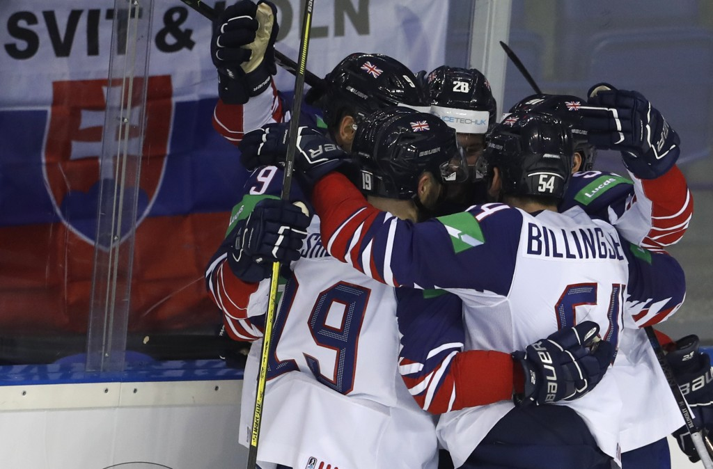 Great Britain's Brett Perlini, right, celebrates with teammates after scoring his sides second goal during the Ice Hockey World Championships group A