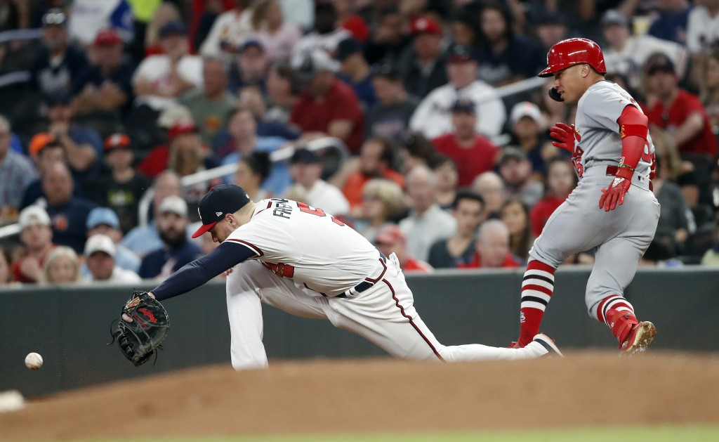 St. Louis Cardinals' Kolten Wong (16) is safe at first base with a single as the ball gets past Atlanta Braves first baseman Freddie Freeman (5) in th