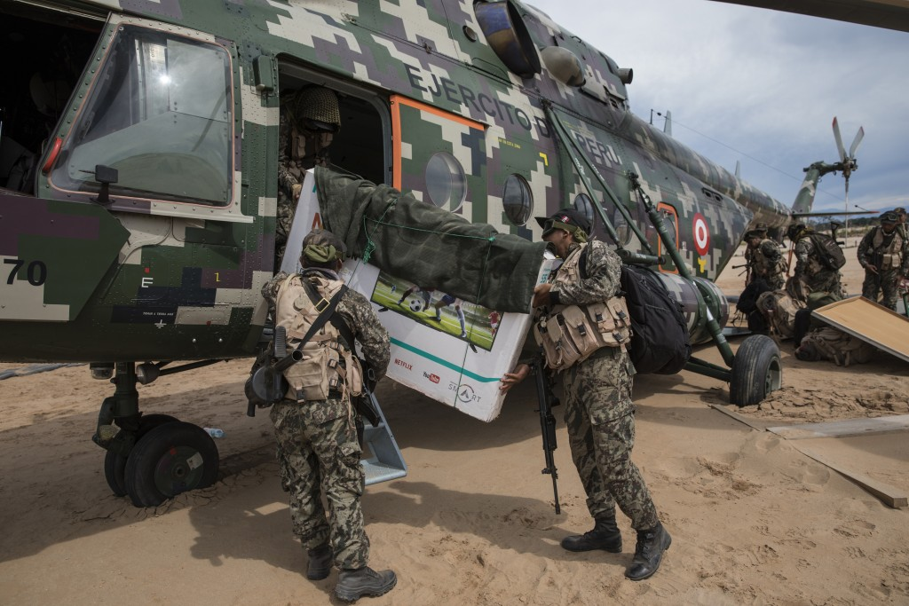 In this April 1, 2019 photo, returning to their home base soldiers load their television in to a military helicopter, on a makeshift airstrip at the B