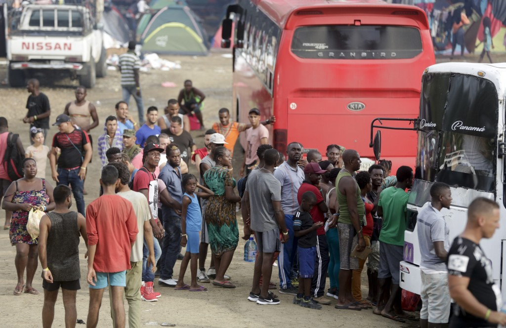 In this May 10, 2019 photo, a group of migrants wait for space in a bus that will take them on their trip north, in Peñitas, Darien Province, Panama.