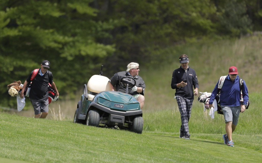 John Daly, second from left, talks with Kelly Kraft, second from right, as they move to the ninth fairway during a practice round for the PGA Champion