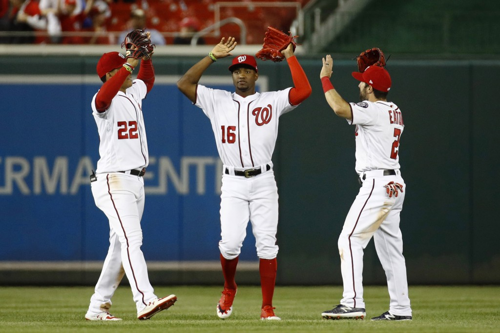 Washington Nationals outfielders Juan Soto, from left, Victor Robles and Adam Eaton celebrate after a baseball game against the New York Mets, Wednesd...