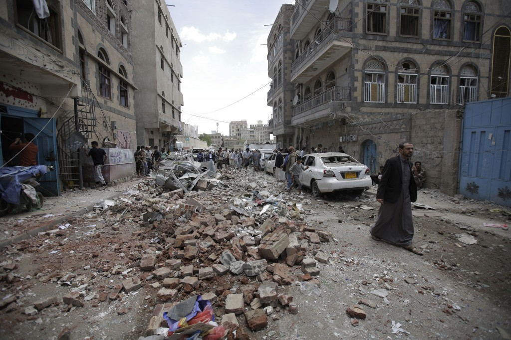 People inspect the site of an airstrike by Saudi-l...