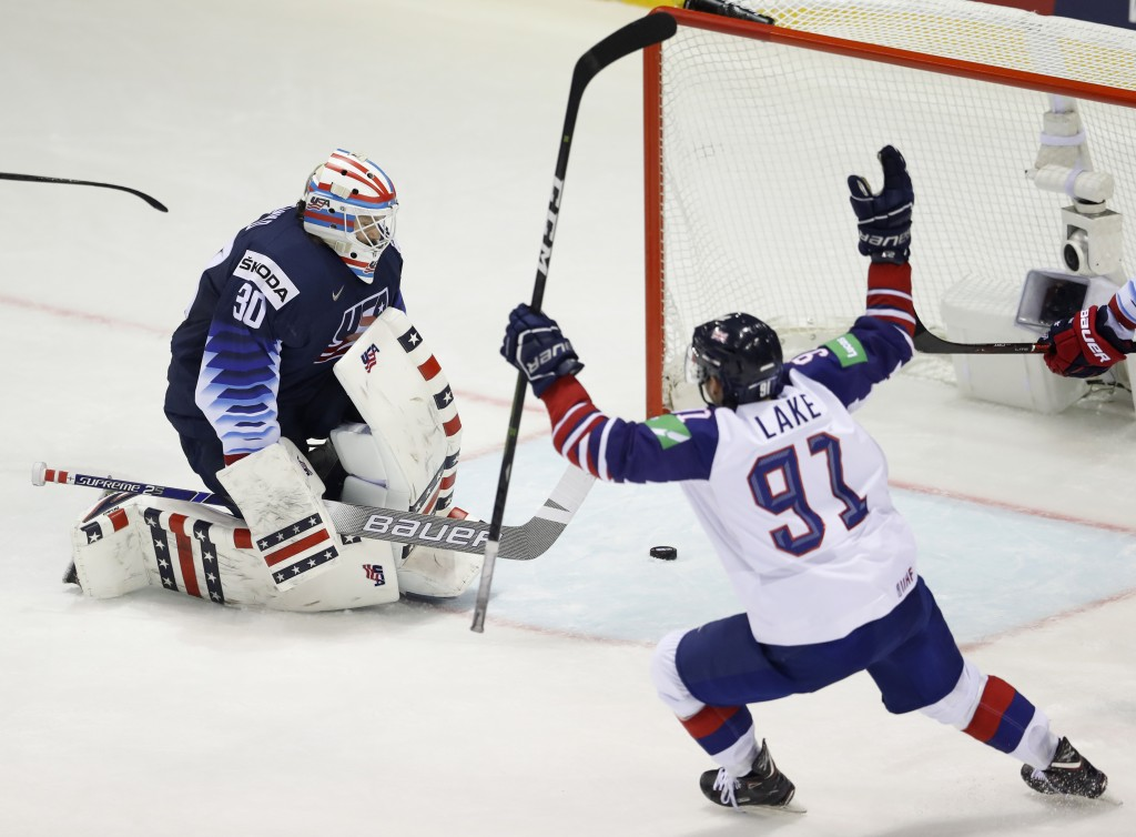 Great Britain's Ben Lake, right, celebrates his sides second goal scored past goaltender Thatcher Demko of the US, left, during the Ice Hockey World C