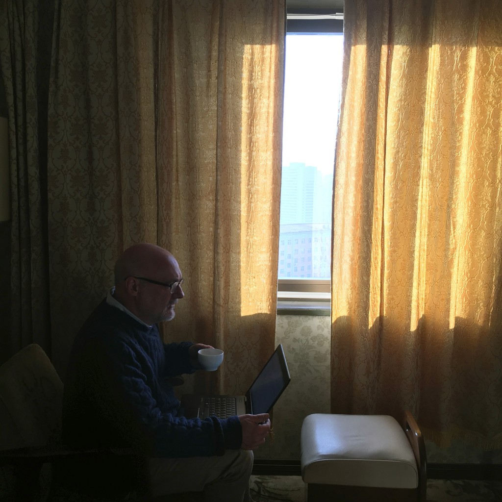 In this Feb. 21, 2016 photo The Associated Press' North Korea Bureau Chief Eric Talmadge works in his hotel room overlooking the skyline of the North ...