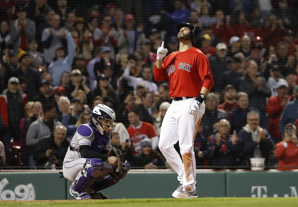 Boston Red Sox's J.D. Martinez points skyward as he crosses home plate in front of Colorado Rockies catcher Tony Wolters after his two-run home run du