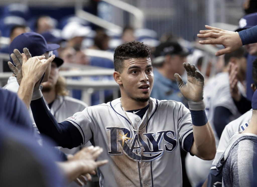 Tampa Bay Rays' Willy Adames is congratulated in the dugout after scoring on a double by Anthony Bemboom in the second inning during a baseball game a