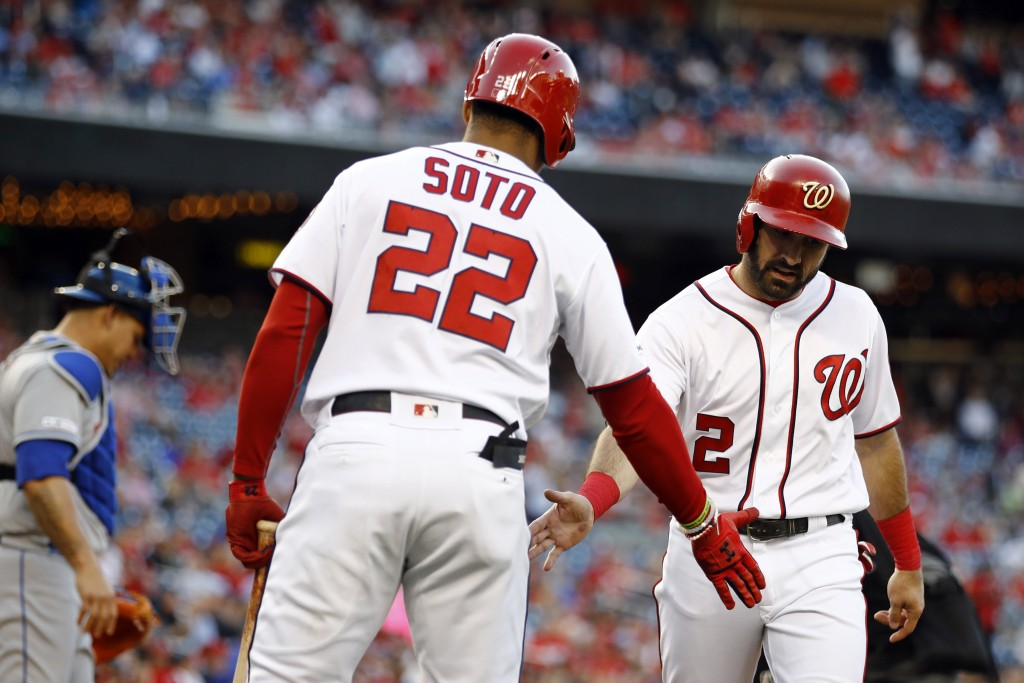 Washington Nationals' Adam Eaton, right, celebrates with teammate Juan Soto after scoring on a ground rule double that was hit by Anthony Rendon in th...