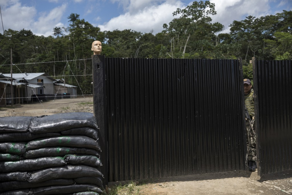 In this March 28, 2019 photo, a soldier peers out from inside a new police and military base in Peru's Tambopata province. Earlier this year, Peru ann...
