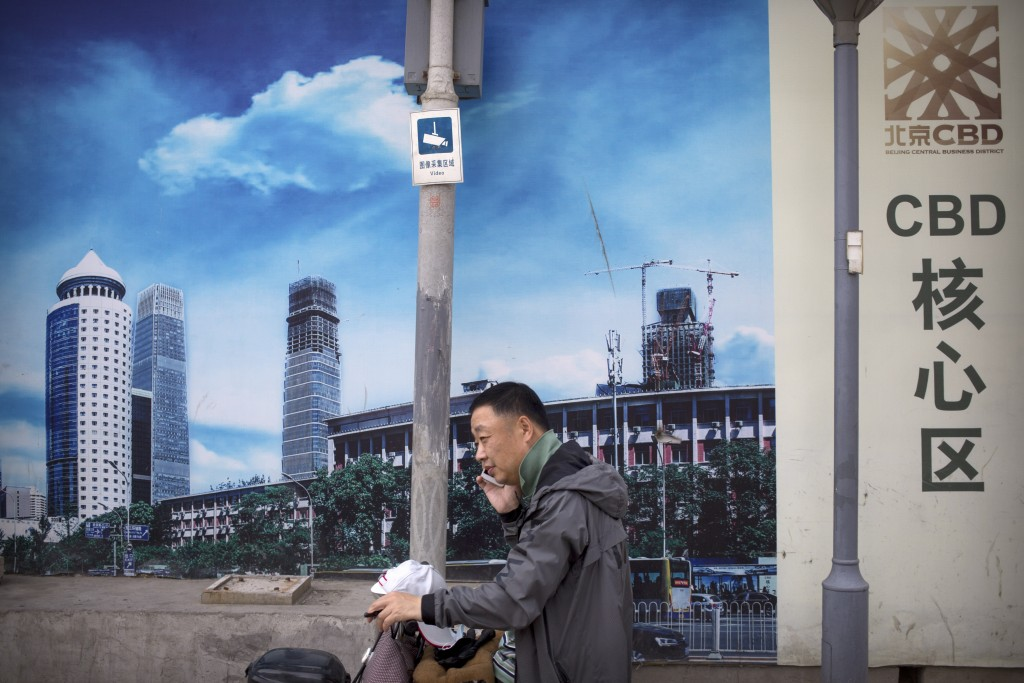 A man uses his mobile phone in front of a billboard at a construction site in Beijing, Thursday, May 16, 2019. Figures released on Wednesday showed Ch...