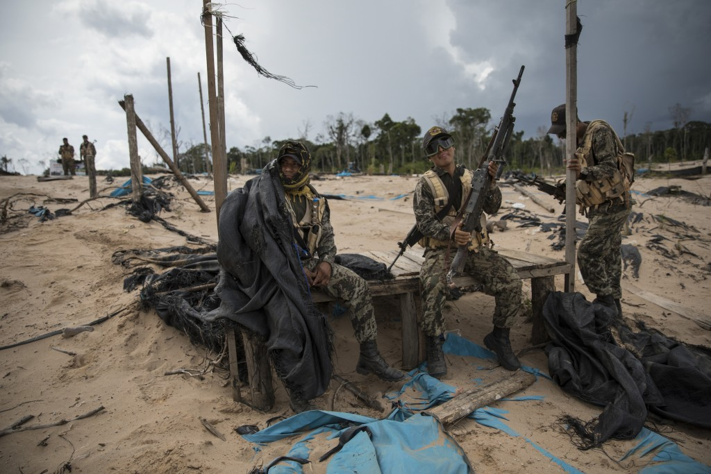In this April 1, 2019 photo, soldiers wait for the arrival of a helicopter bringing supplies and replacements, on a makeshift airstrip of the Balata p...