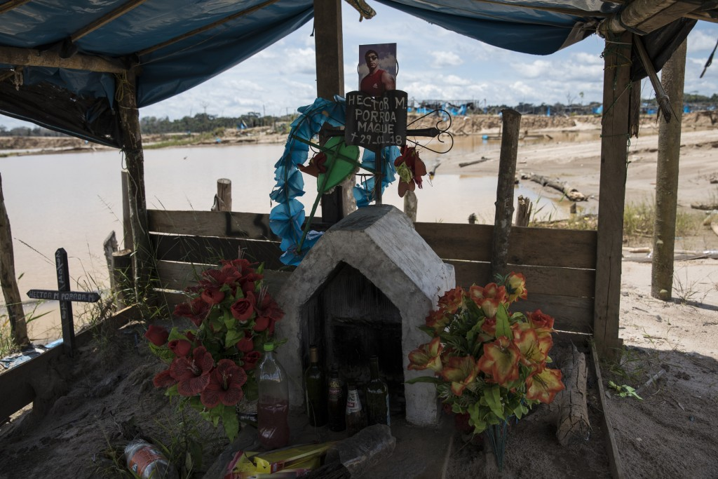 This March 28, 2019 photo shows a memorial adorned with artificial flowers and bottles of alcohol inside a former illegal gold mining camp that has be