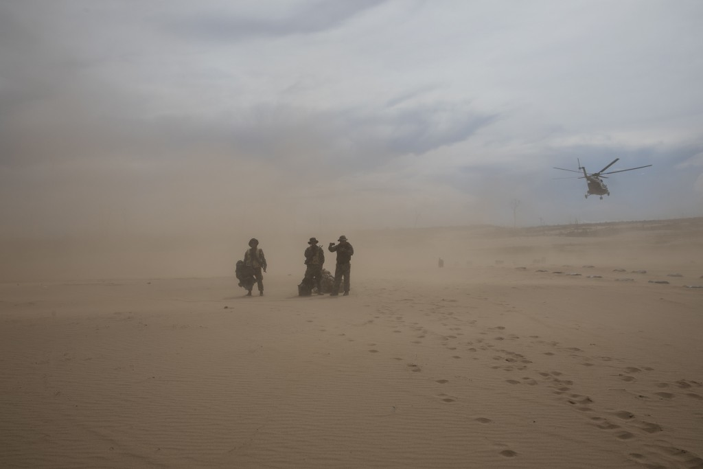 """This April 1, 2019 photo shows """"Operation Mercury"""" soldiers arriving for their new assignment standing in a dust cloud on a makeshift airstrip at the"""