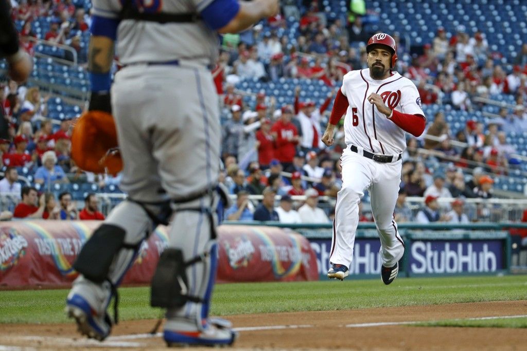 Washington Nationals' Anthony Rendon races home toward New York Mets catcher Wilson Ramos for a run on Howie Kendrick's single in the first inning of ...