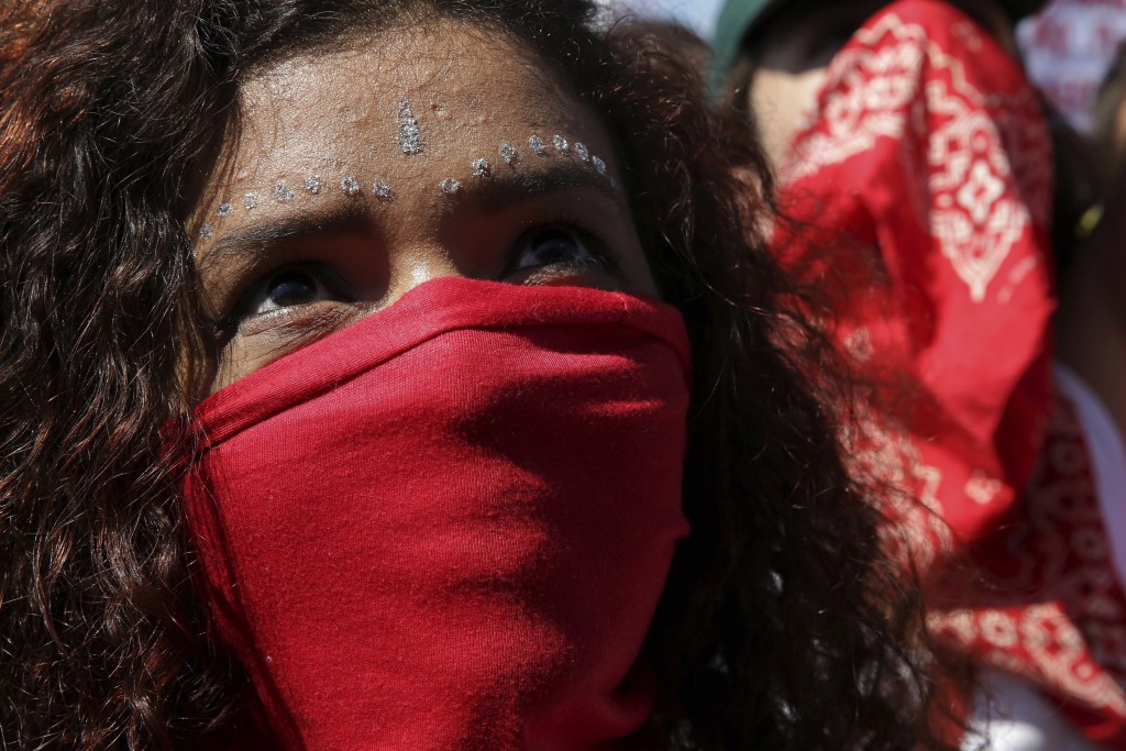 A masked student takes part in a nation-wide education strike, in Brasilia, Brazil, Wednesday, May 15, 2019. Federal education officials this month an...