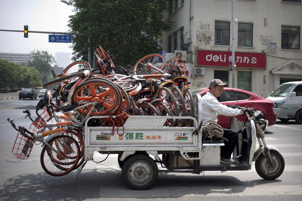 In this Thursday, May 16, 2019, file photo, a worker uses an electric cart to haul a load of ride-sharing bicycles along a street in Beijing. Figures