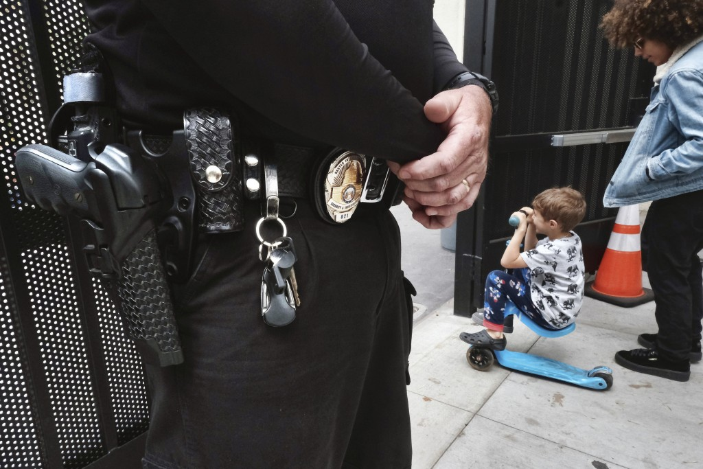 In this Monday May 13, 2019 photo, a security guard stands on watch at Beverly Hills Unified School District's K-8 Horace Mann School as students prep