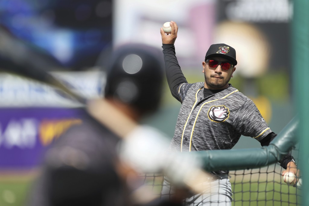 In this Monday, May 13, 2019 photo, Quad Cities River Bandits manager Ray Hernandez, right, throws during batting practice before a Class-A Midwest Le