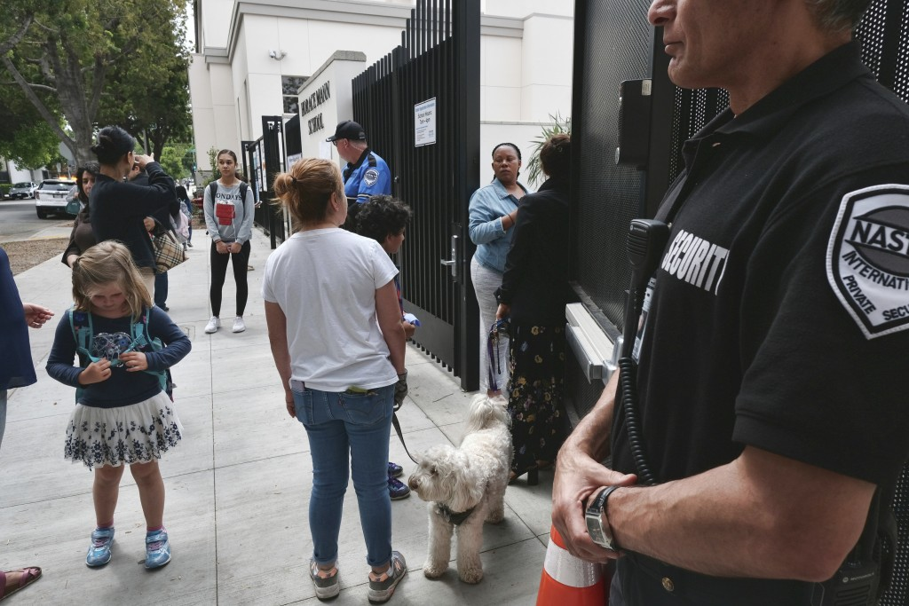 In this Monday May 13, 2019 photo, a security guard stands watch as parents pick up their children after school at Beverly Hills Unified School Distri
