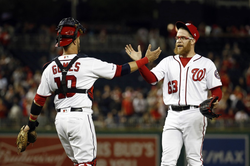 Washington Nationals catcher Yan Gomes, left, and relief pitcher Sean Doolittle celebrate after closing out a baseball game against the New York Mets,...