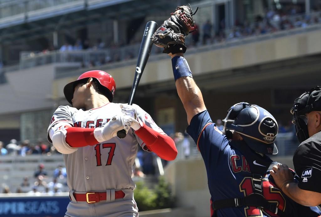 Los Angeles Angels' Shohei Ohtani, left, rears back on a pitch by Minnesota Twins pitcher Jake Odorizzi as Minnesota Twins catcher Jason Castro reache