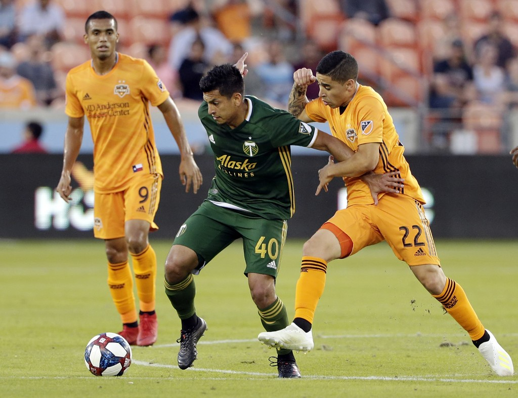 Portland Timbers midfielder Renzo Zambrano (40) moves the ball between Houston Dynamo forward Mauro Manotas (9) and midfielder Matias Vera (22) during