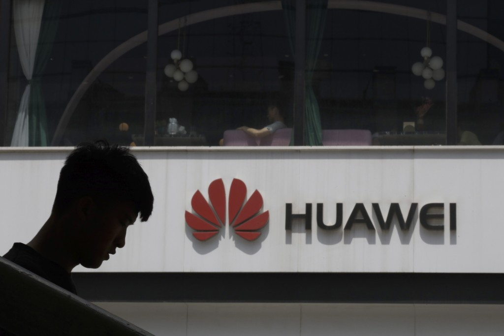 A Chinese man is silhouetted near the Huawei logo in Beijing on Thursday, May 16, 2019. In a fateful swipe at telecommunications giant Huawei, the Tru...