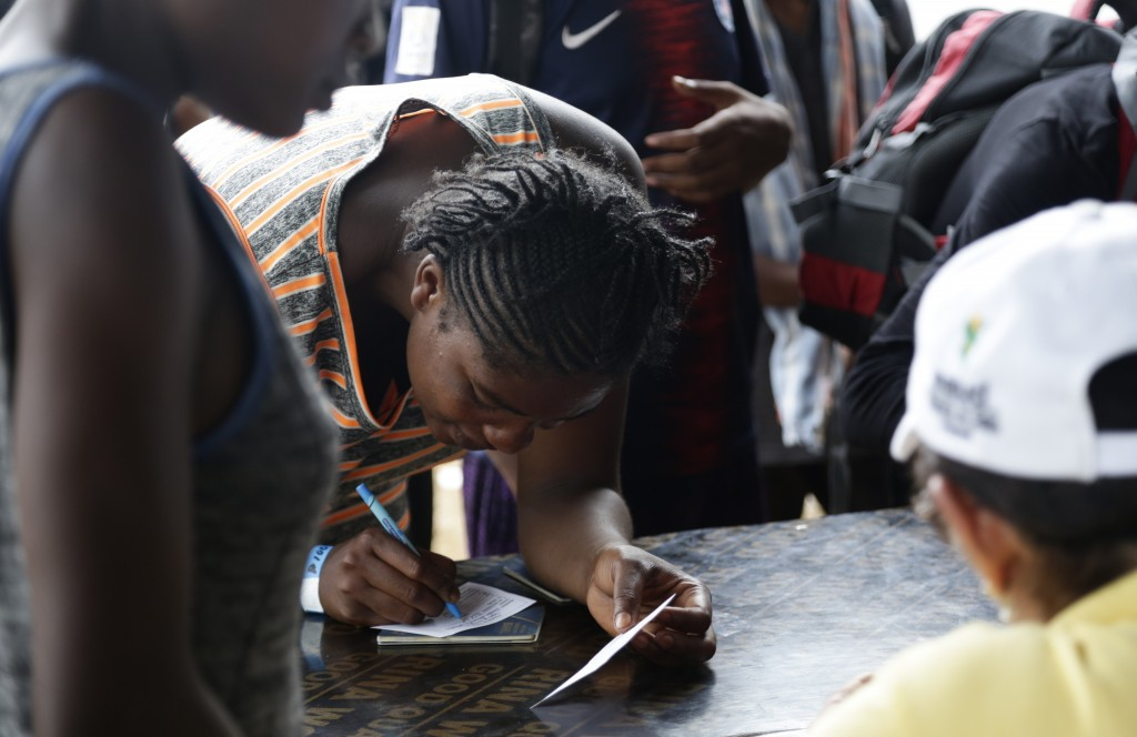 In this May 10, 2019 photo, a migrant signs a docu...