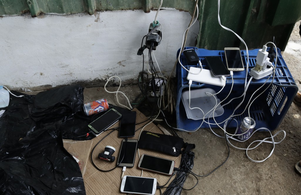 In this May 10, 2019 photo, migrant's cell phones charge their batteries at a shelter in Peñitas, Darien Province, Panama. These days Peñitas is overw