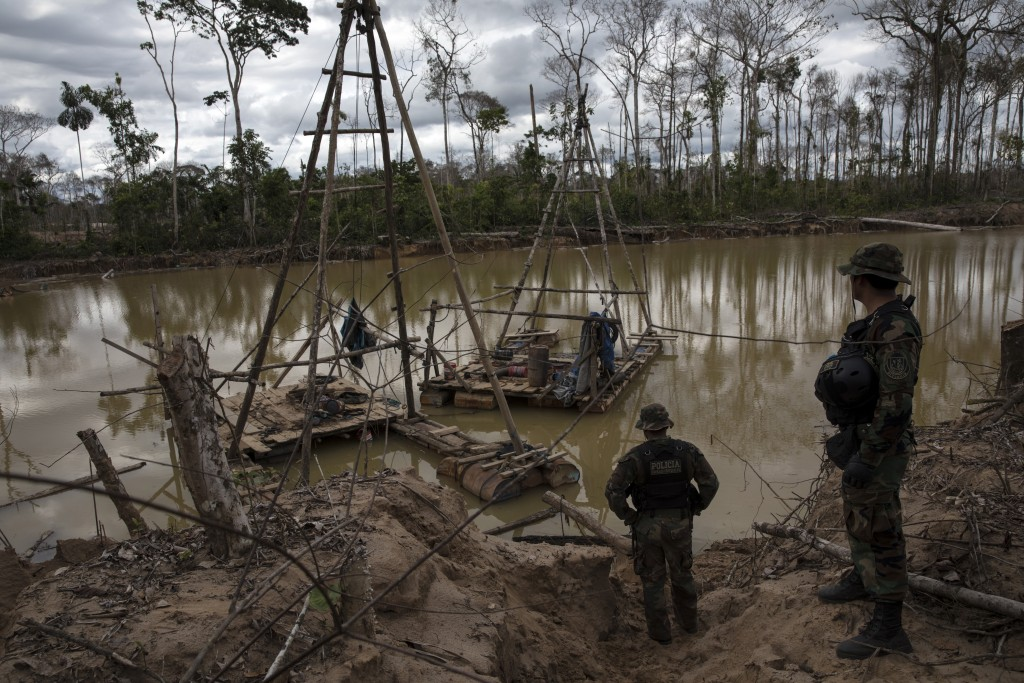 "In this April 1, 2019 photo, police special forces stand next to illegal mining machinery in Peru's Tambopata province. As part of ""Operation Mercury""..."
