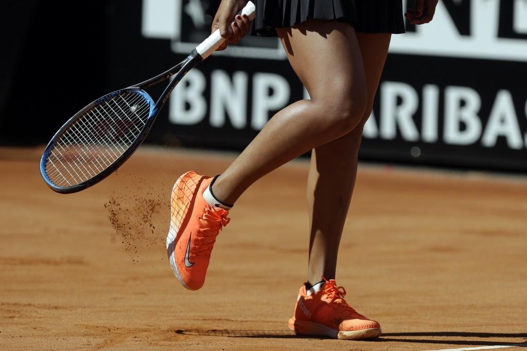 Japan's Naomi Osaka removes the court soil away from her shoe during her match against Slovakia's Dominika Cibulkova at the Italian Open tennis tourna