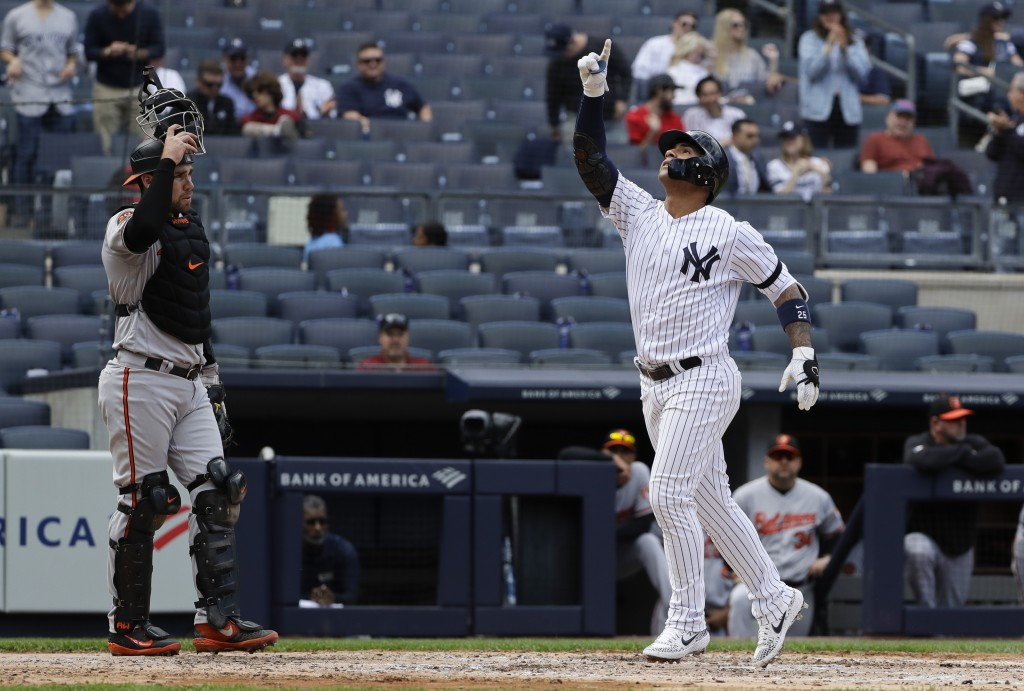 New York Yankees' Gleyber Torres, right, gestures as he runs past Baltimore Orioles catcher Austin Wynns, left, after hitting a home run during the fo