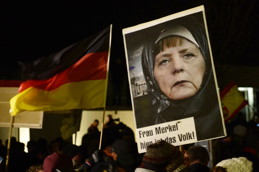 FILE - In this Jan. 12, 2015 file photo, a protestor holds a poster with a manipulated image of German Chancellor Angela Merkel wearing a headscarf an