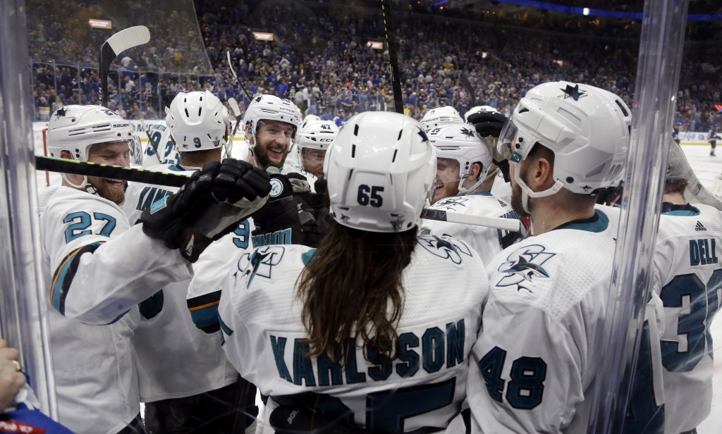 San Jose Sharks defenseman Erik Karlsson (65), of Sweden, is congratulated after scoring the winning goal against the St. Louis Blues during overtime