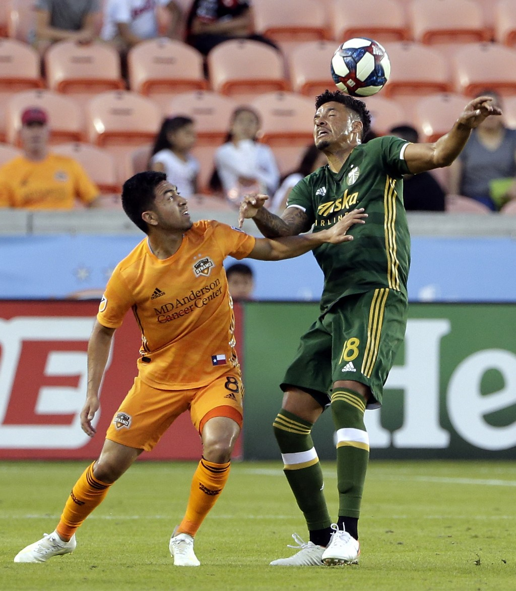 Houston Dynamo midfielder Memo Rodriguez (8) pushes off Portland Timbers defender Julio Cascante (18) as he gets the header during the first half of a