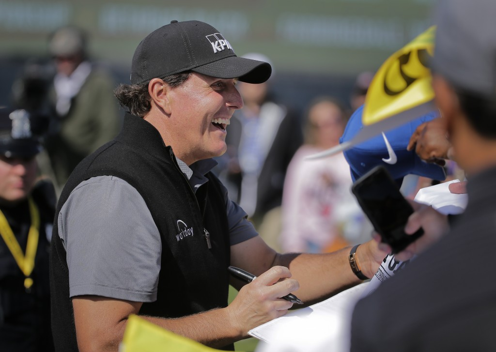 Phil Mickelson reacts as he signs autographs after finishing a practice round for the PGA Championship golf tournament, Wednesday, May 15, 2019, at Be