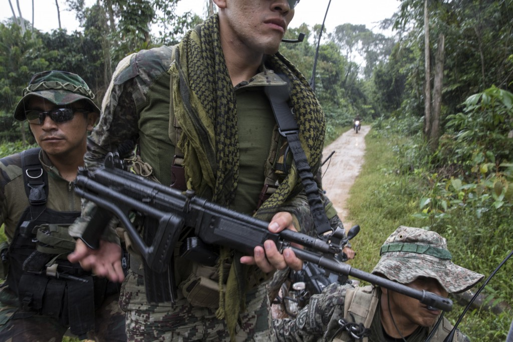 """In this March 27, 2019 photo, """"Operation Mercury"""" special forces patrol an area after the destruction of machinery used by illegal miners in the Tambo"""