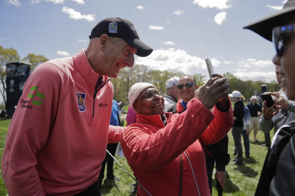 Jim Furyk, left, poses for a photo with a fan during a practice round for the PGA Championship golf tournament, Wednesday, May 15, 2019, at Bethpage B